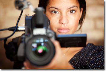 Woman camera operator behind video camera