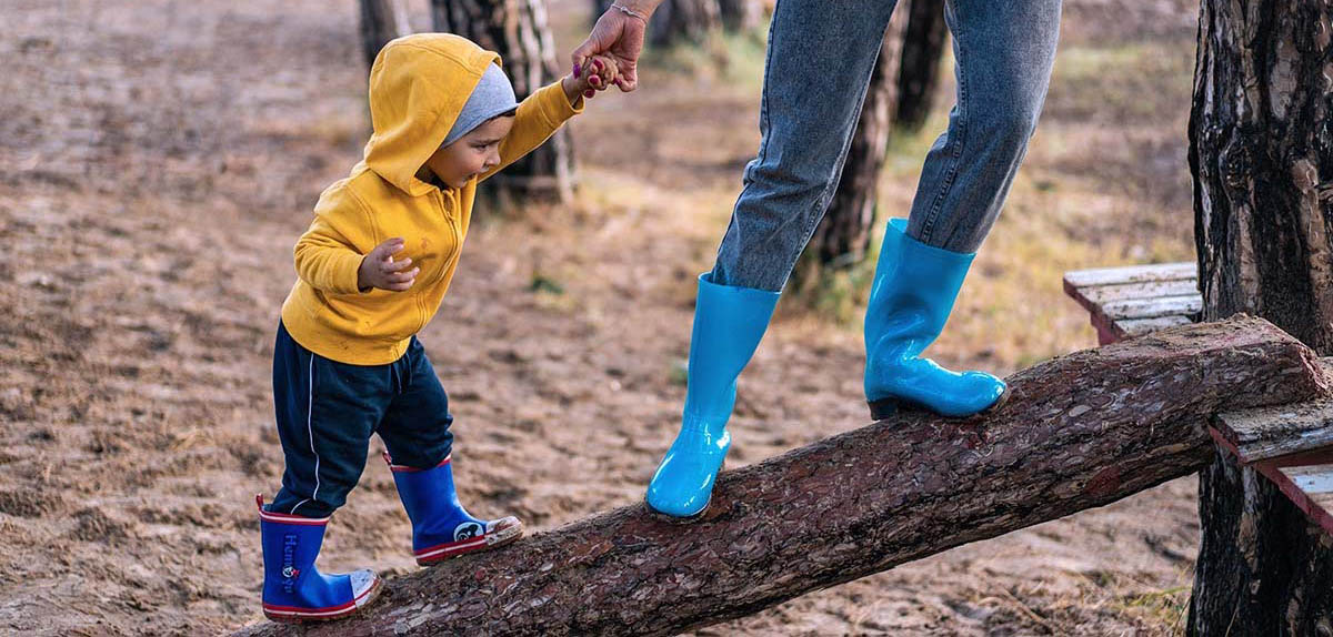 Image of child being helped by an adult to walk across a log