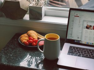 Image of a laptop on a desk. Next to it there is a cup of coffee and some food.
