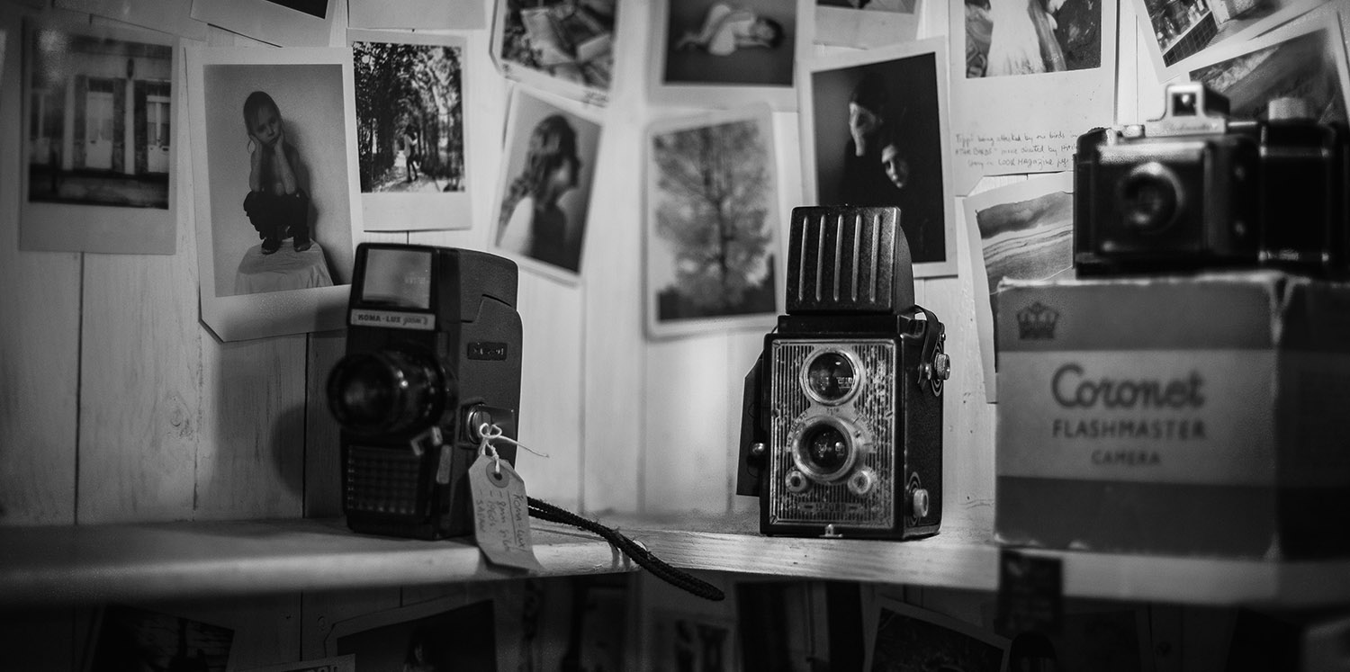 Black and white image of old cameras with developed pictures hanging on the wall in the background.