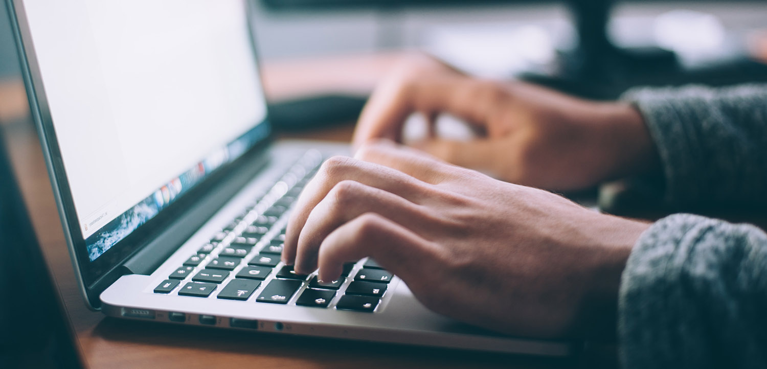 Close-up image of a person typing on a computer.