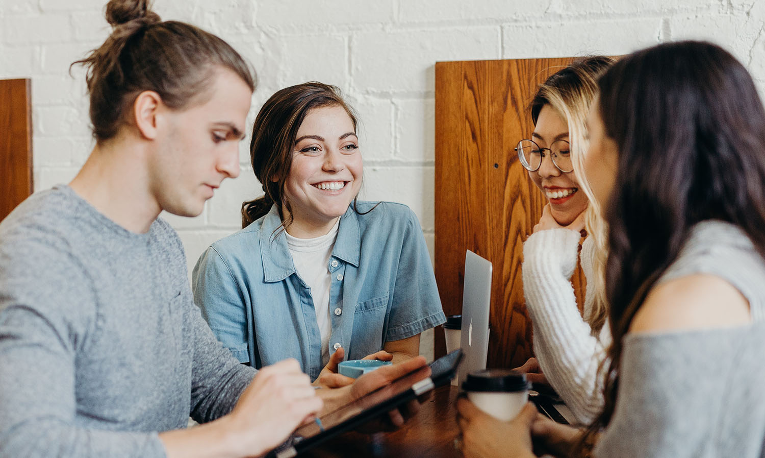 Image of students studying and smiling together at a desk space.