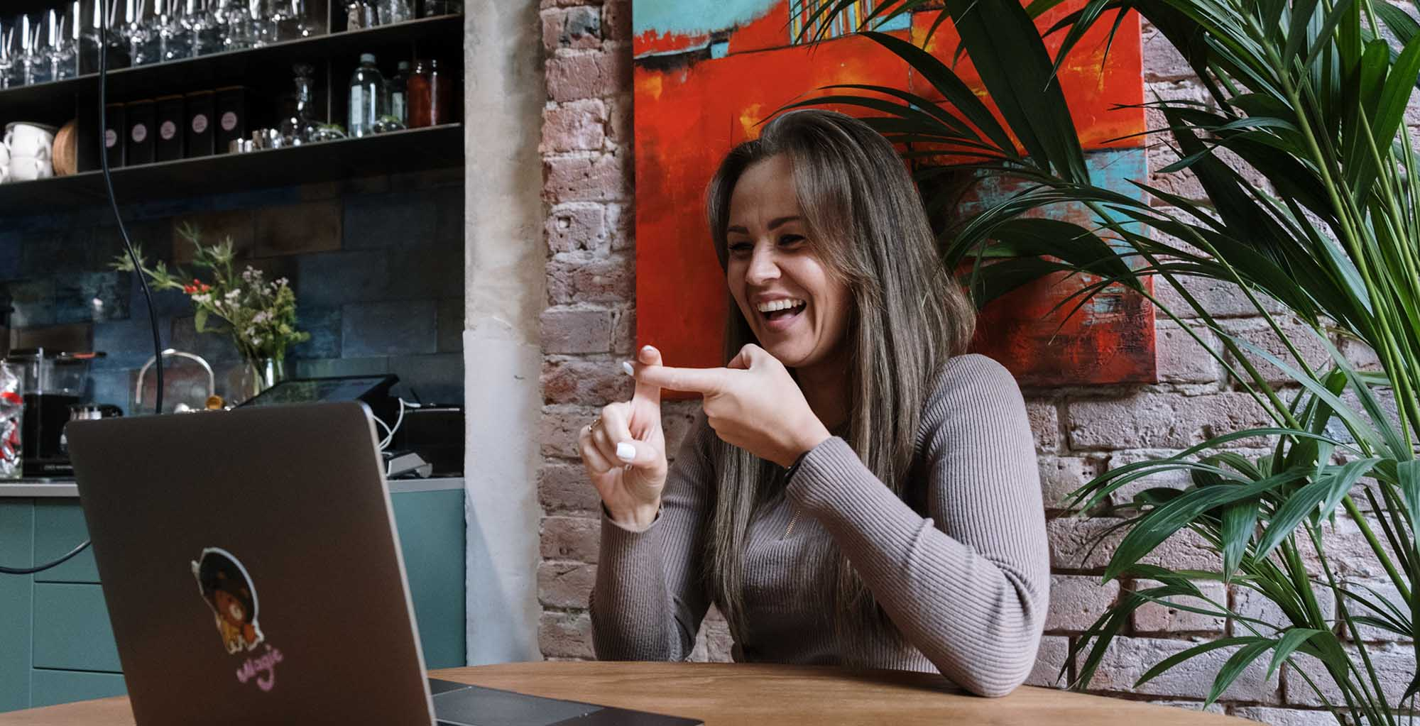 Image of a woman speaking sign language with someone through her laptop.