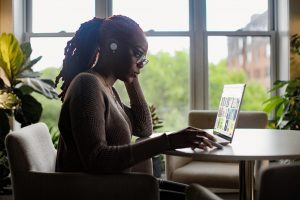 Image of a woman using a laptop at a desk space.